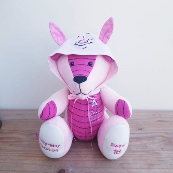 Keepsake Memory Bear - Image of a keepsake bear, made from a pink Piglet onesie. The hood is up and there are pointed ears atop it.