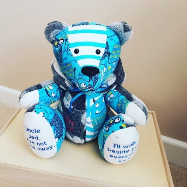 Keepsake Memory Bear - Image of a keepsake memory bear, made from blue coloured children's clothing with embroidered feet.