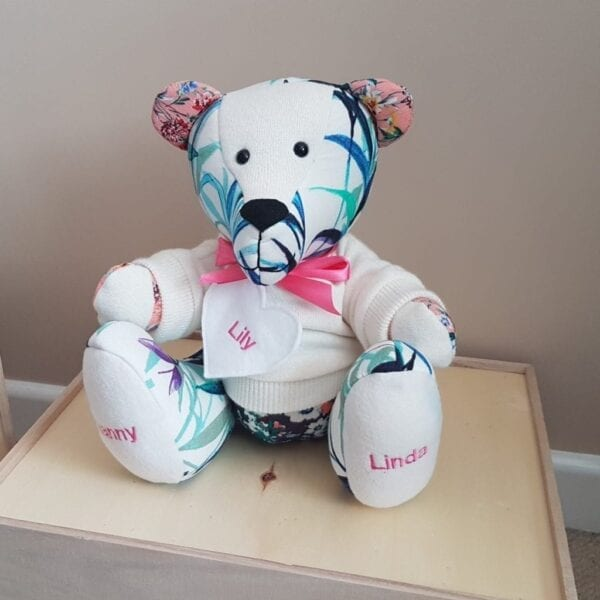 Keepsake Memory Bear - Image of a keepsake memory bear, made from a white plain fabric and a pink/green floral fabric, with a bow tie at the neck and embroidery on the feet.