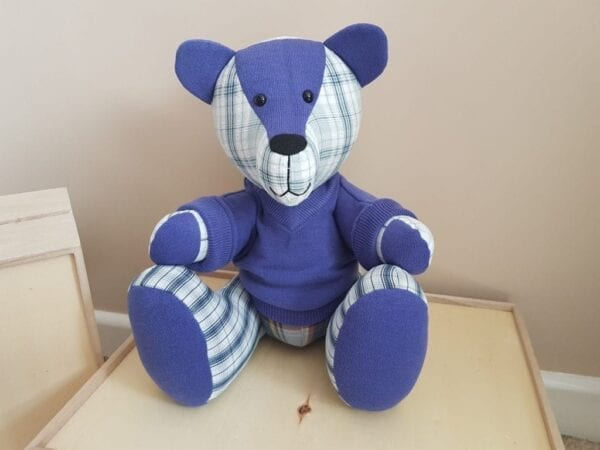 Keepsake Memory Bear - Image of a keepsake memory bear, made from plain purple and beige checked fabric, with a purple knitted jumper.