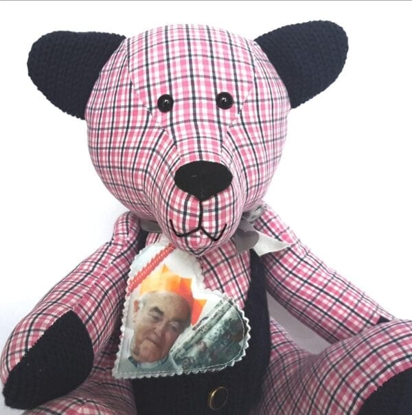 Photo Memory Bear - Close up image of a photo keepsake memory bear, made from a red and blue check fabric, wearing a fabric photo heart around the neck.