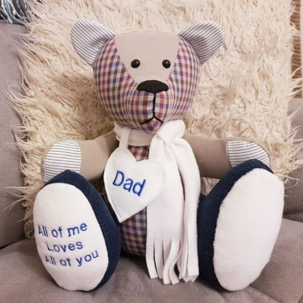 Ashes Memory Bear - Image of a keepsake memory bear, made from a red and beige check fabric, wearing a scarf and a personalised heart around the neck.