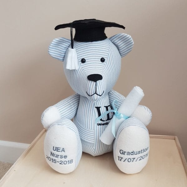 Graduation Memory Bear - Image of a keepsake memory bear, made from a white and blue student nurse uniform, with embroidered feet and a university crest on the chest, wearing a black mortarboard hat and holding a scroll.
