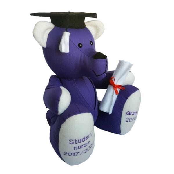 Graduation Memory Bear - Side view image of a keepsake memory bear, made from a purple student nurse uniform, with embroidered feet, wearing a black mortarboard hat and holding a scroll.