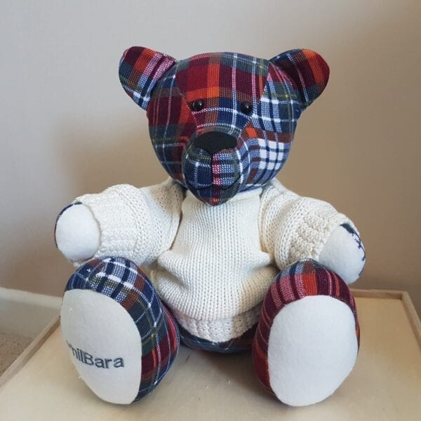 Memorial Memory Bear - Image of a keepsake memory bear, made from a red and blue check fabric, wearing a cream knitted jumper with an embroidered paw.