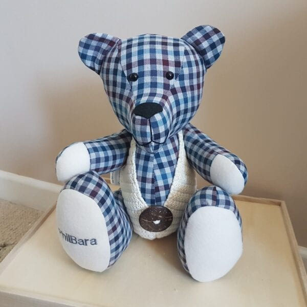 Memorial Memory Bear - Image of a keepsake memory bear, made from a white and blue check fabric, wearing a cream knitted waistcoat with an embroidered paw.