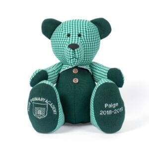School Memory Bear - Image of a keepsake bear made from school uniform (a green and white checked dress and a green knitted jumper), with embroidery and a school crest to the feet.