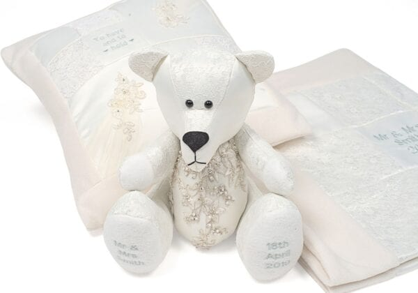 Wedding Memory Bear - Image of wedding dress memory bear, made from a lace gown, with embroidered feet and a crystal detail section to the chest sat in front of a wedding dress cushion and blanket.