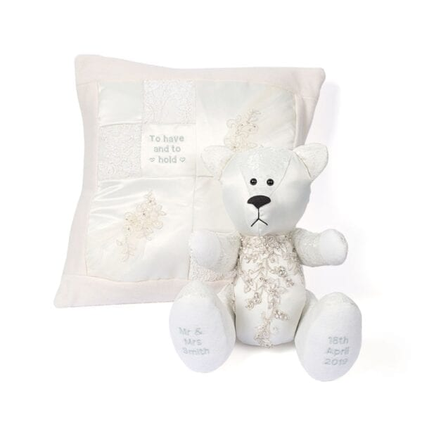Wedding Memory Bear - Image of wedding dress memory bear, made from a lace gown, with embroidered feet and a crystal detail section to the chest sat in front of a wedding dress cushion.
