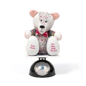 Weighted Memory Bear - Image of a weighted keepsake bear sat on a set of scales, with different patterned floral and spotty fabrics, a pink bow tie at the neck and embroidery on the feet.