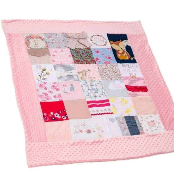 Bobble Memory Blanket: Image of a pink bobble fleece blanket, made from baby clothes laid out flat.