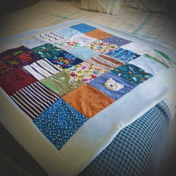 Fleece Memory Blanket: Image of a blue fleece blanket, made from baby clothes laid out flat on a bed.