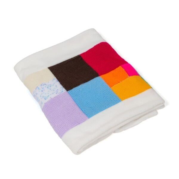 Fleece Memory Blanket: Image of a folded patchwork fleece blanket made from multicoloured knitted clothes.