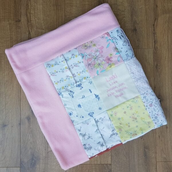 Fleece Memory Blanket: Image of a folded pink fleece blanket made from baby clothes.